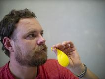A man with a beard and mustache is preparing to inflate a yellow balloon stock images