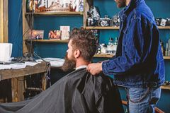 Man with beard and mustache sits in barbershop, beauty supplies on background. Barbershop concept. Man bearded client of royalty free stock image