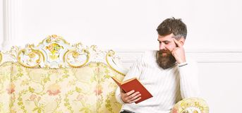 Man with beard and mustache sits on baroque style sofa, holds book, white wall background. Macho on smiling face. Passionate about reading book. Reader concept stock photography