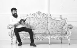 Man with beard and mustache sits on baroque style sofa, holds book, white wall background. Macho on smiling face. Passionate about reading book. Guy reading old stock photo