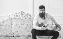 Man with beard and mustache sits on baroque style sofa, holds book, white wall background. Reflections on literature. Concept. Guy thinking about literature royalty free stock photography