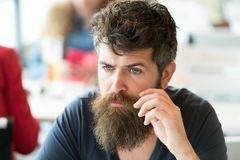 Man with beard and mustache sits outdoor at cafe terrace. Bearded man on concentrated face touches mustache. Hipster Royalty Free Stock Photography