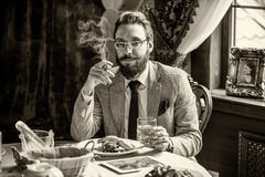 Man with a beard and mustache, smoking a cigar during dinner Royalty Free Stock Photos