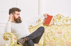 Man with beard and mustache spends leisure with book. Scientist, professor on strict face analyzing literature. Self. Education concept. Lecturer sit on sofa royalty free stock images