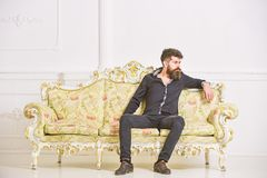 Man with beard and mustache spends leisure in luxury living room. Hipster on thoughtful face sits alone. Rich and lonely. Concept. Owner of luxury apartment royalty free stock image