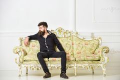 Man with beard and mustache spends leisure in luxury living room. Hipster on thoughtful face sits alone. Rich and lonely. Concept. Owner of luxury apartment stock photo