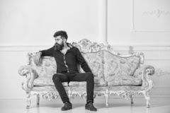 Man with beard and mustache spends leisure in luxury living room. Hipster on thoughtful face sits alone. Rich and lonely. Concept. Owner of luxury apartment stock photos