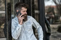 Man with beard and mustache on strict face talking, building on background. Bearded man speaking on cell phone. Communication concept. Hipster with beard speak royalty free stock images