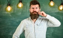 Man with beard and mustache on thoughtful face stand in front of chalkboard. Guy thinking with thoughtful expression. Intellectual task concept. Bearded royalty free stock image