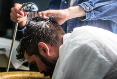 Man with beard and mustache with towel on shoulders, male hands with shower on background. Man bearded client of hipster. Barbershop. Barbers hands washing hair Stock Photos
