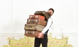 Man with beard and mustache wearing classic suit delivers luggage, luxury white interior background. Butler and service. Concept. Macho elegant on surprised stock photo