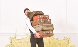 Man with beard and mustache wearing classic suit delivers luggage, luxury white interior background. Butler and service. Concept. Macho elegant on surprised stock images