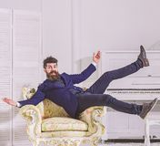 Man with beard and mustache wearing fashionable classic suit, sits, jumps on old fashioned armchair. Macho attractive. And elegant on cheerful face and happy royalty free stock image
