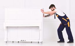 Man with beard and mustache, worker in overalls pushes piano, white background. Courier delivers furniture in case of stock photo