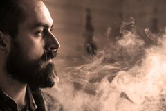 Man with Beard and Mustages Vaping an Electronic Cigarette. Vaper Hipster Smoke Vaporizer and Exhals Smoke Rings. Young Man with Beard and Mustages Vaping an stock photo