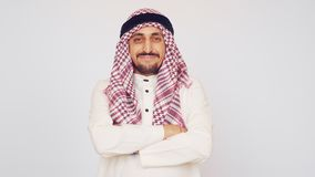 A man with a beard and national dress smiling. An Arab in a modern office. He folded his hands and smiles widely. The stock video footage