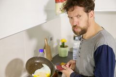 Funny man in kitchen not able to cook an egg royalty free stock images