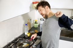 Man in kitchen in the morning cooking breakfast yawning stock photo