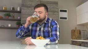 A man with a beard on a plaid shirt sits in the kitchen and drinks beer with chips, the pleasure of eating, slow-mo stock video footage