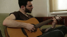 A man with a beard playing the guitar. An attractive man with a black beard and mustache playing the acoustic guitar. He is sitting cross-legged on an olive stock video