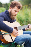 Man with beard playing guitar in camping Stock Photo