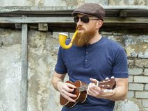 Man with beard playing ukulele and smoking a pipe stock image