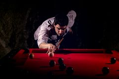 A man with a beard plays a big billiard. Party in 12-foot pool. Billiards in the club game for men. A man with a cue breaks the pyramid Stock Image