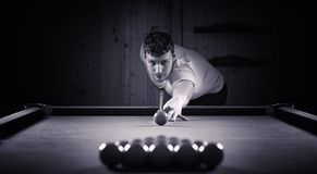 A man with a beard plays a big billiard. Party in a 12-foot pool Stock Images