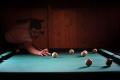 A man with a beard plays a big billiard. Party in a 12-foot pool Stock Photo