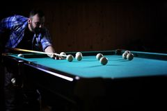 A man with a beard plays a big billiard. Party in a 12-foot pool. A man with a beard plays a big billiard. Party in 12-foot pool. Billiards in the club game for Stock Photography