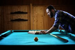 A man with a beard plays a big billiard. Party in a 12-foot pool. A man with a beard plays a big billiard. Party in 12-foot pool. Billiards in the club game for Royalty Free Stock Images