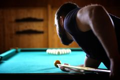 A man with a beard plays a big billiard. Party in a 12-foot pool royalty free stock photos