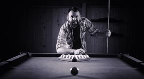 A man with a beard plays a big billiard. Party in a 12-foot pool royalty free stock photography