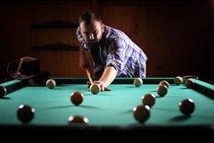 A man with a beard plays a big billiard. Party in a 12-foot pool. A man with a beard plays a big billiard. Party in 12-foot pool. Billiards in the club game for Stock Photo