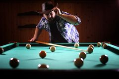 A man with a beard plays a big billiard. Party in a 12-foot pool. A man with a beard plays a big billiard. Party in 12-foot pool. Billiards in the club game for Royalty Free Stock Image