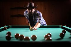 A man with a beard plays a big billiard. Party in a 12-foot pool royalty free stock images
