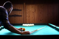A man with a beard plays a big billiard. Party in a 12-foot pool stock photos