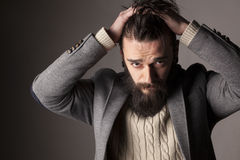Man with beard. Portrait of a sad young man with beard and mustache and his hands in his hair Stock Photography