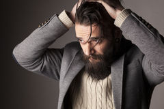 Man with beard. Portrait of a sad young man with beard and mustache and his hands in his hair Royalty Free Stock Images