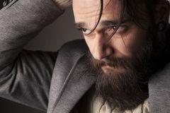 Man with beard. Portrait of a sad young man with beard and mustache and his hands in his hair Royalty Free Stock Photography