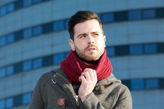 Man with beard posing outside city building with jacket ad scarf Royalty Free Stock Image