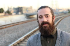 Man With Beard posing with train track background looking towards the horizon Royalty Free Stock Images