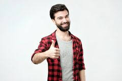Man with beard, raising thumbs up and smiling broadly, giving positive feedback. Pleased and satisfied male with beard, raising thumbs up and smiling broadly stock images