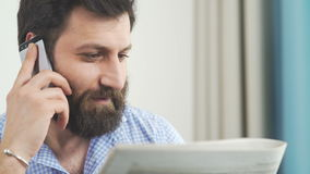 Man with beard is reading a newspaper and y talking on the phone. stock footage