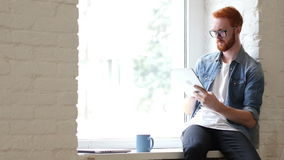 Man with Beard and Red Hairs Using Tablet for Work and Browsing Information. Creative designer , businessman stock video footage