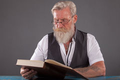 Man with beard reding a book Stock Photography