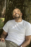 Man with beard relaxing. An image of a man with a beard relaxing under a tree Royalty Free Stock Image