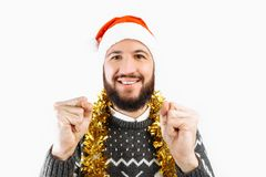 A man with a beard in a Santa Claus hat holding Christmas balls, Christmas-tree decorations royalty free stock photography