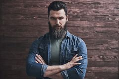 Man with beard. Serious bearded man in casual clothes is standing with crossed arms on a wooden background stock photos