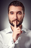 Man with beard showing silent sign. Handsome man with beard showing silent sign. studio portrait over dark background Royalty Free Stock Images